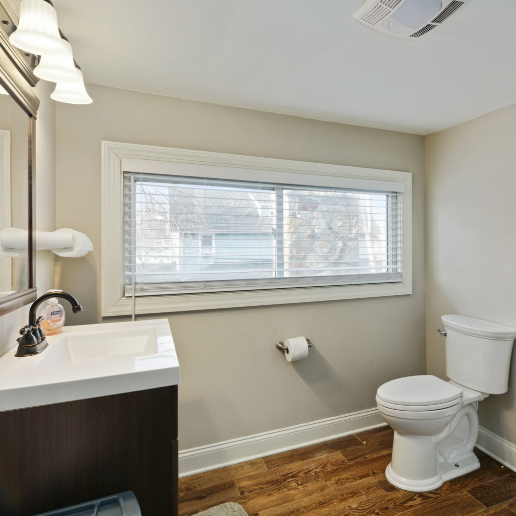 updated bathroom with chic wood flooring single toilet and vanity Full kitchen stylishly designed with seating and updated appliances at Somerdale Sober Living Homes for Men
