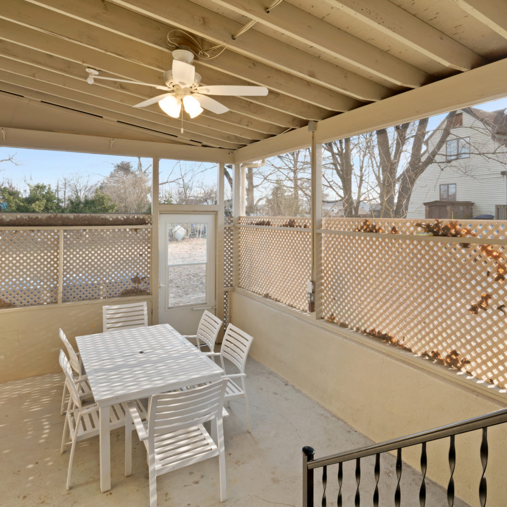 Outdoor porch area with seating and door to yard at Full kitchen stylishly designed with seating and updated appliances at Somerdale Sober Living Homes for Men