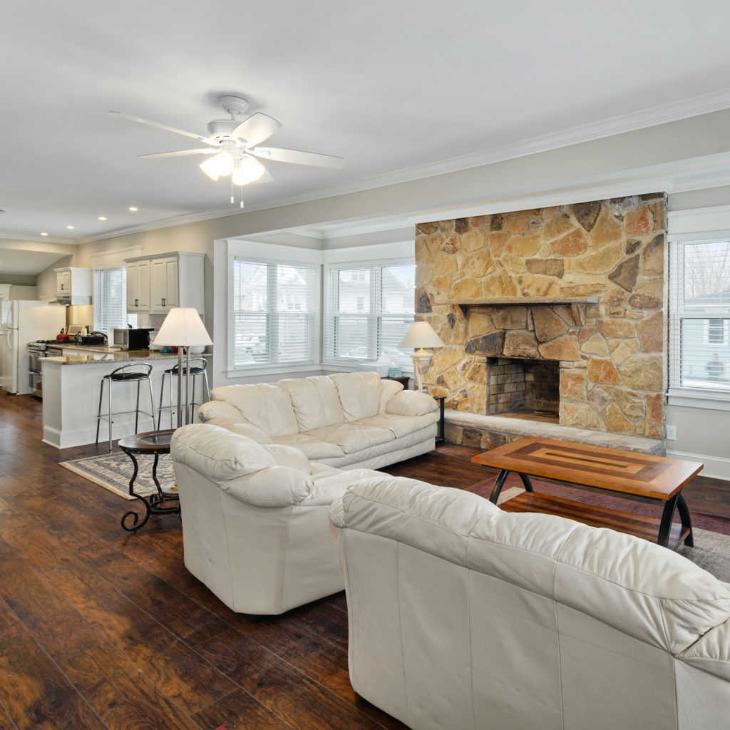 Renovated kitchen and living room space with fireplace and leather seating at Full kitchen stylishly designed with seating and updated appliances at Somerdale Sober Living Homes for Men