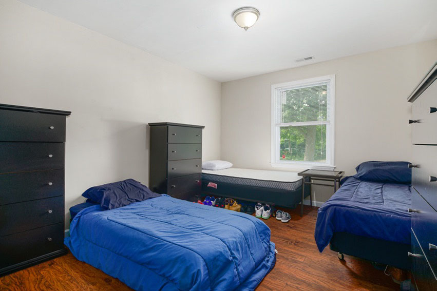Bed room with three beds and three chest of drawers at updated Bathroom with shower at Hi Nella Sober Living Home for Men